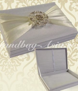 white boxed wedding invitation with large brooch embellishment