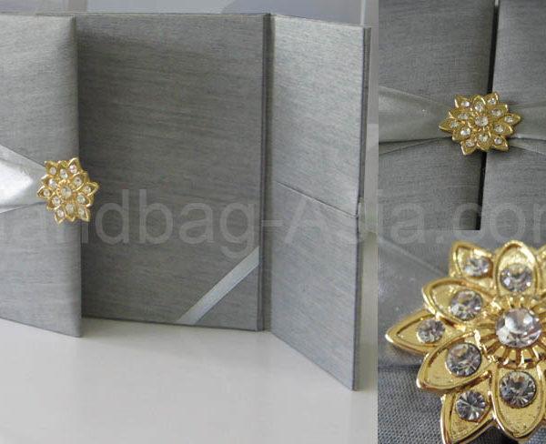 silver wedding portfolio with golden star brooch