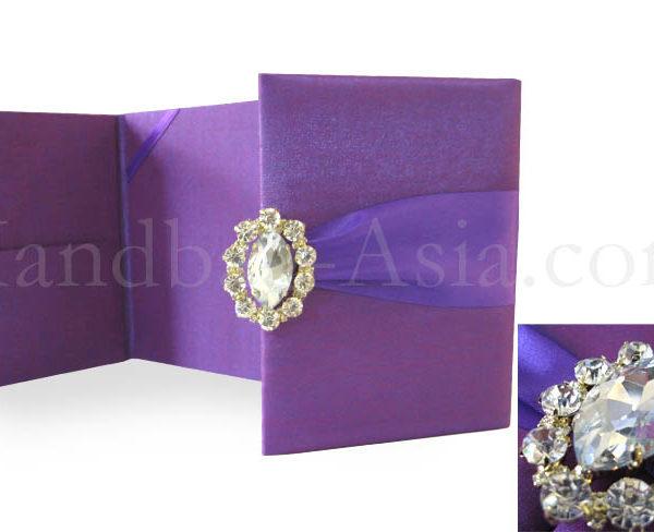 Purple wedding invitation folder with brooch