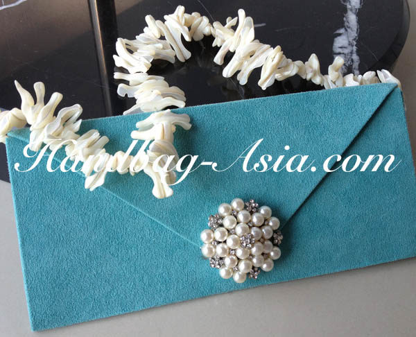 embellished evening clutch bag with pearl brooch